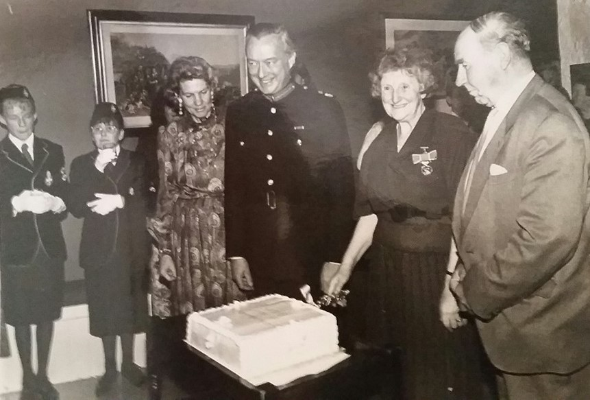 photo of Captain Mary Beaton cutting the cake at her BEM Presentation